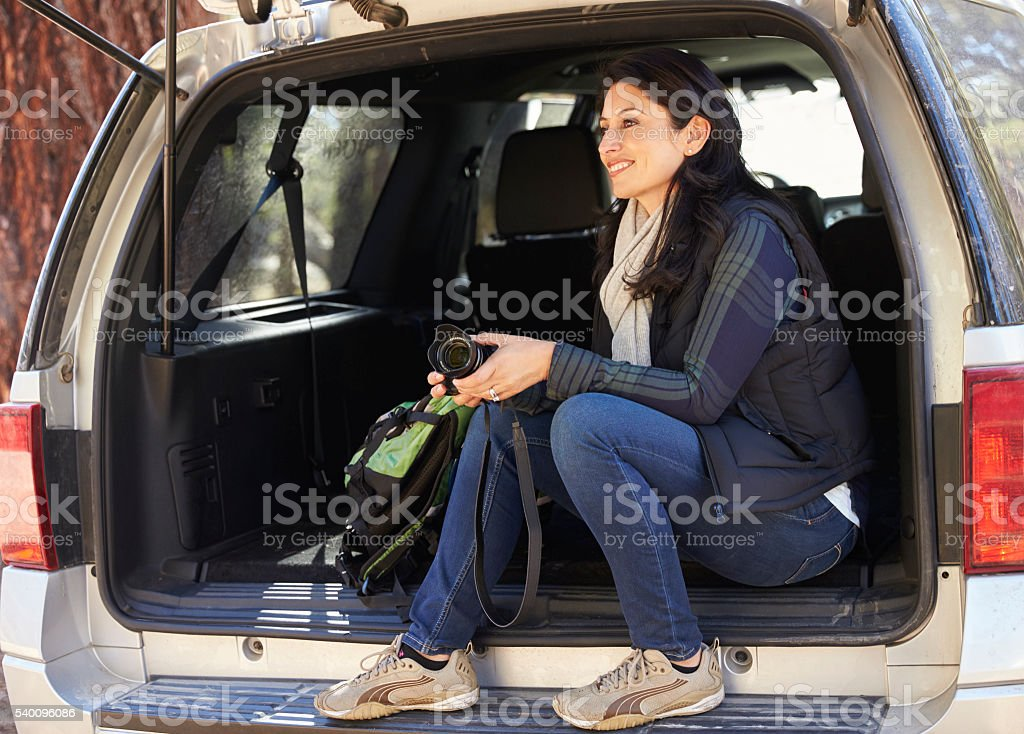 Woman holding camera sits in the open back of a car stock photo