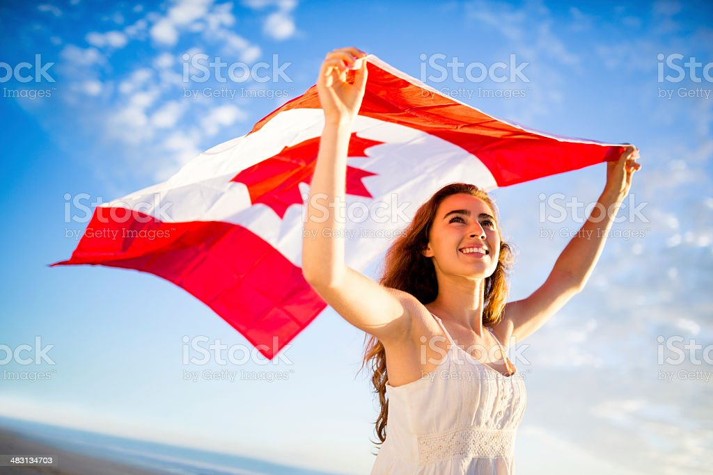 Woman holding canadian flag against sky stock photo