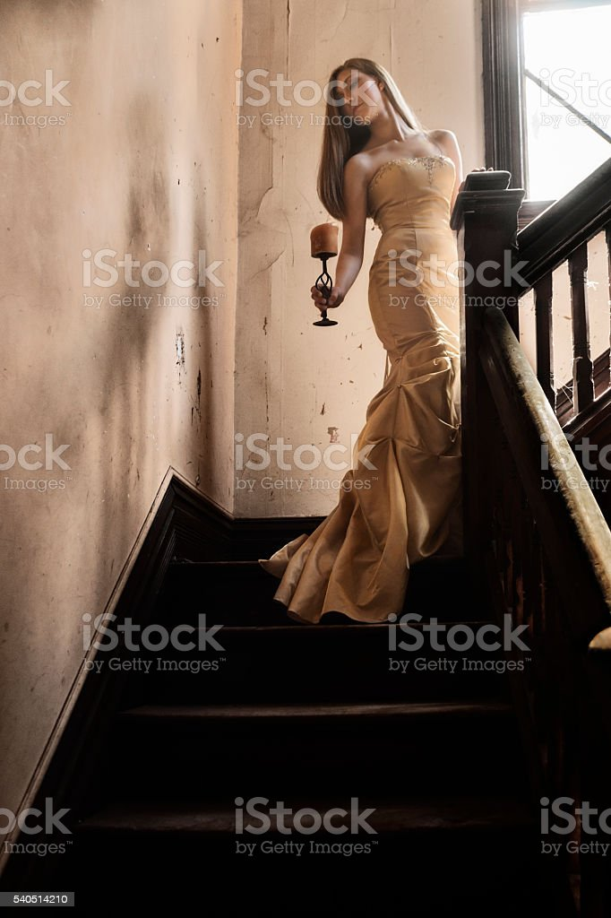 Woman holding candle on staircase stock photo