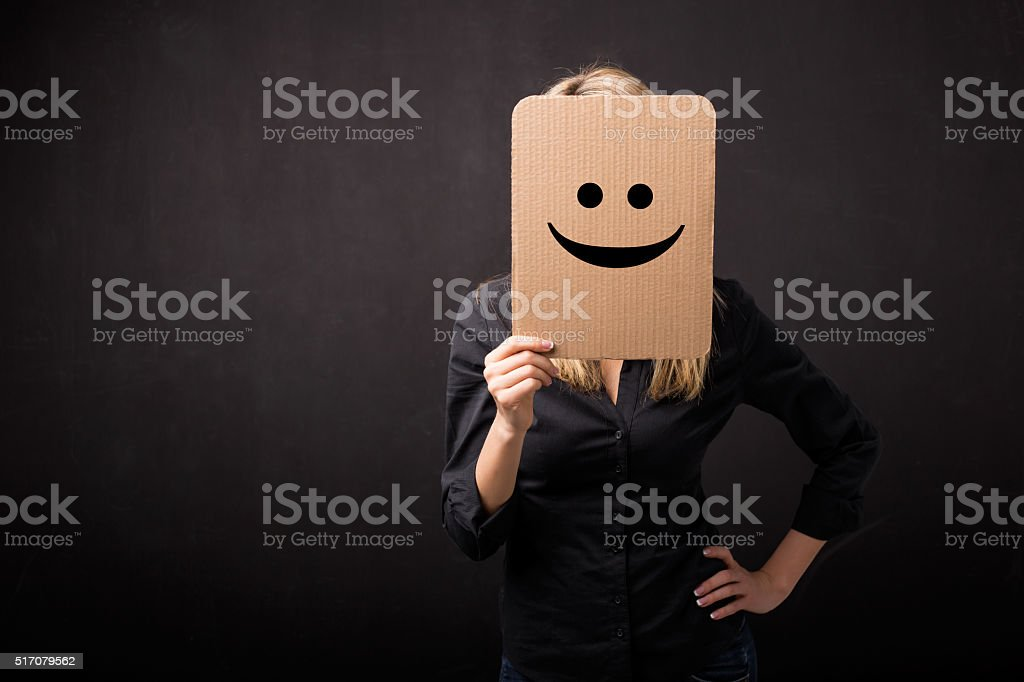 Woman holding cardboard with smiley in front of her face stock photo