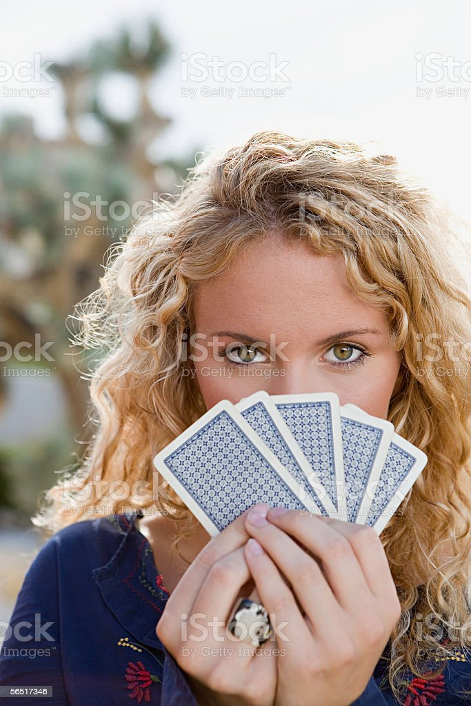 Woman holding cards to her face stock photo