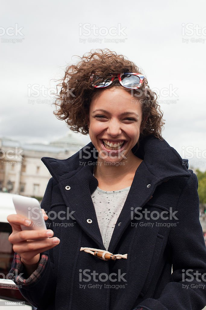 Woman holding cell phone on double decker bus below monument royalty-free stock photo