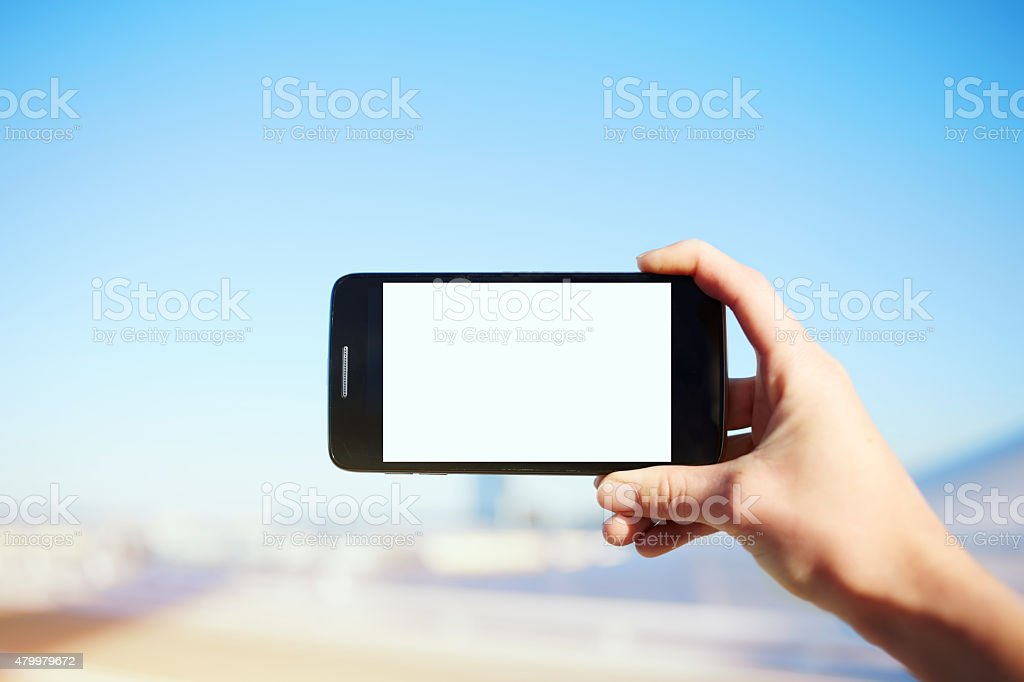 Woman holding cell phone while taking a photograph of landscape stock photo