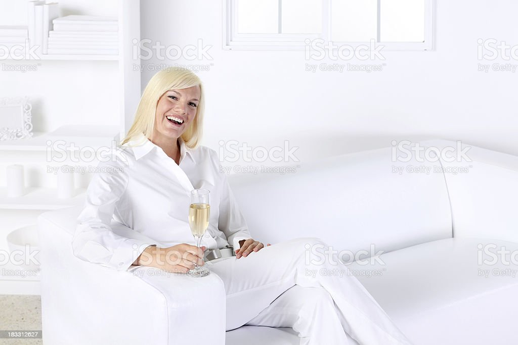 Woman holding champagne flute and smiling royalty-free stock photo