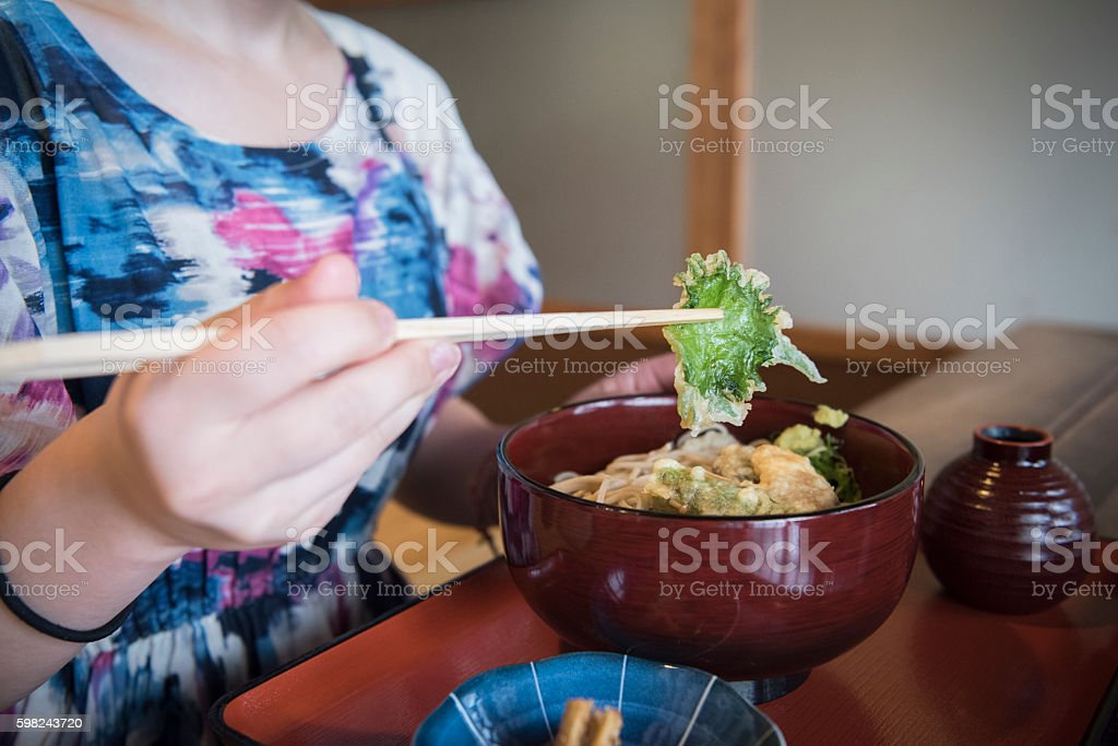 Woman holding chopsticks eating tempura Japanese food stock photo