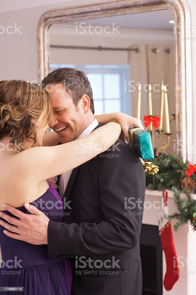 Woman holding Christmas gift and hugging man royalty-free stock photo