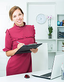 woman holding clipboard in hands in office