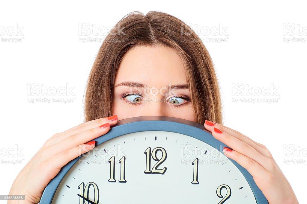 Woman holding clock  with wondering eyes foolishly. stock photo
