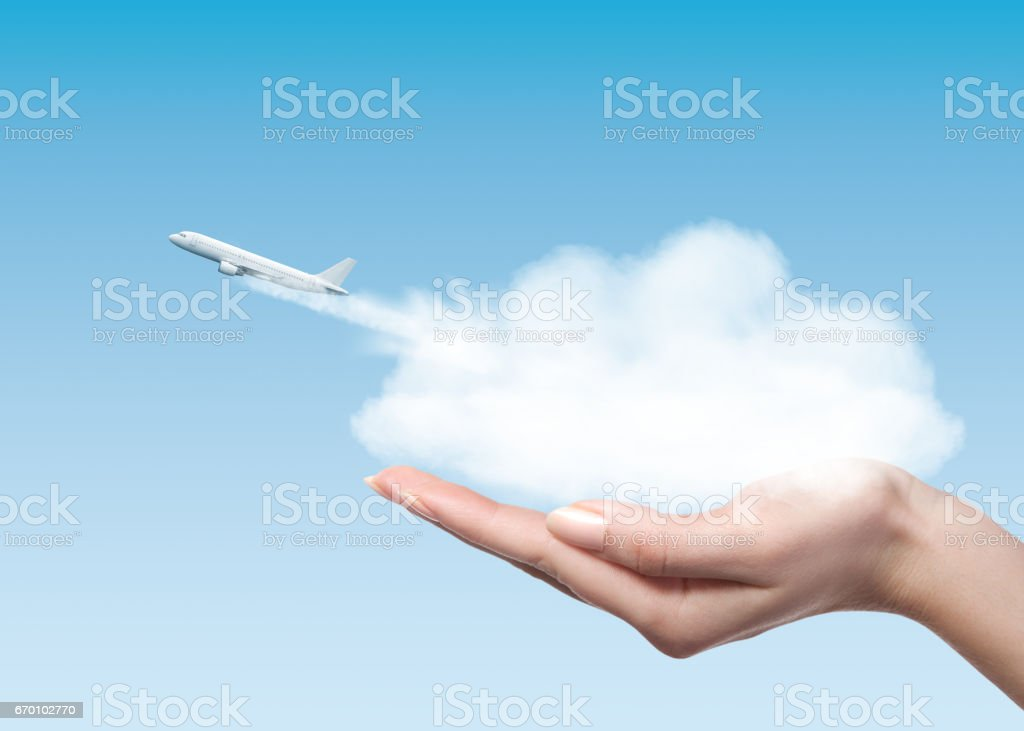 Woman holding cloud with plane taking off stock photo