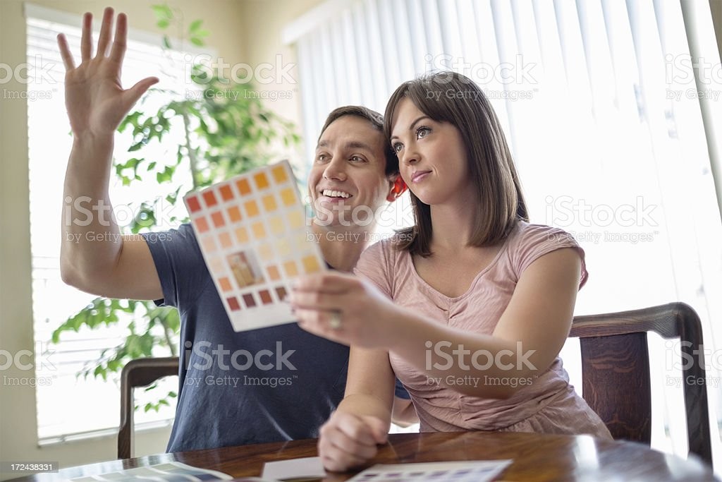Woman Holding Color Swatch While Man Gesturing stock photo