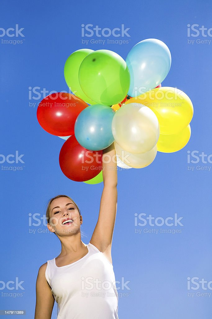 Woman holding colored balloons against blue sky royalty-free stock photo