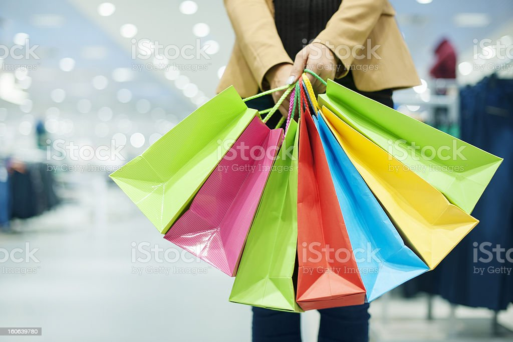 Woman holding colorful shopping bags in a department store stock photo