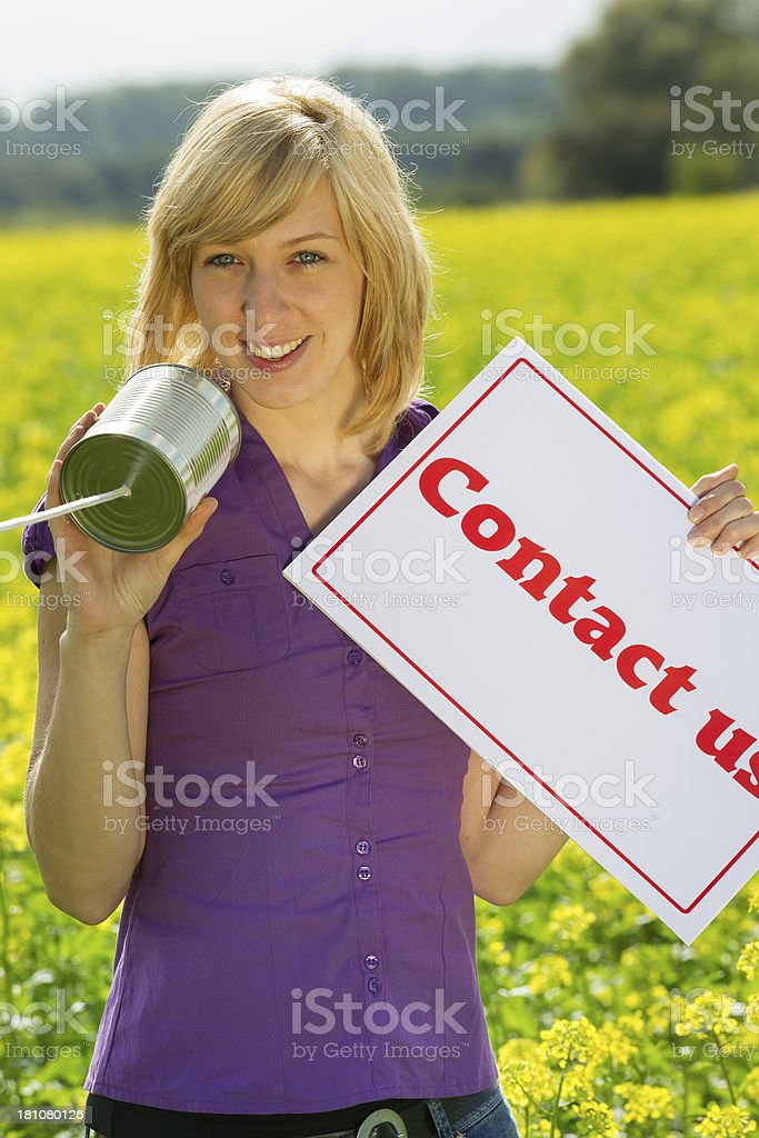 Woman Holding Contact Us Sign And Tin Can Phone royalty-free stock photo