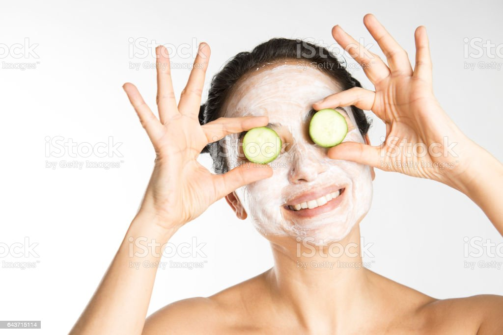 Woman holding cucumber over eyes stock photo