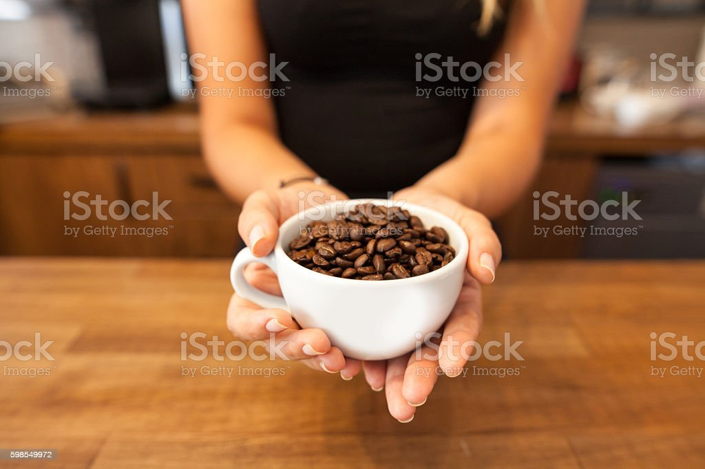 woman holding cup of coffee beans stock photo