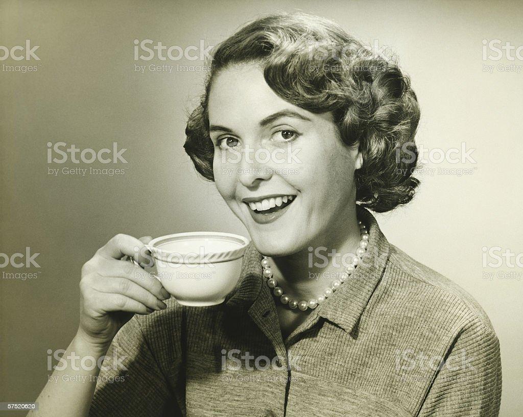 Woman holding cup, posing in studio, (B&W), portrait stock photo