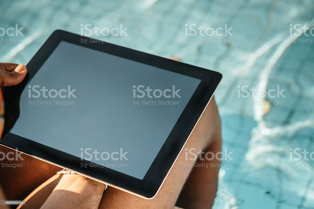woman holding digital tablet sitting at swimming pool stock photo