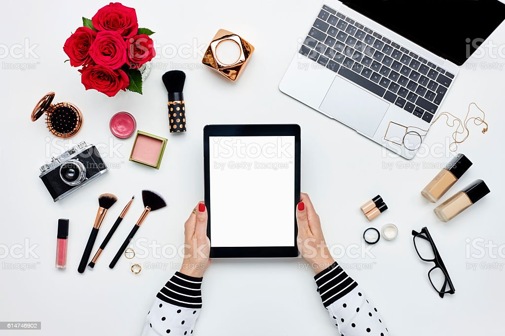 Woman holding digital tablet surrounded with beauty products and technologies stock photo