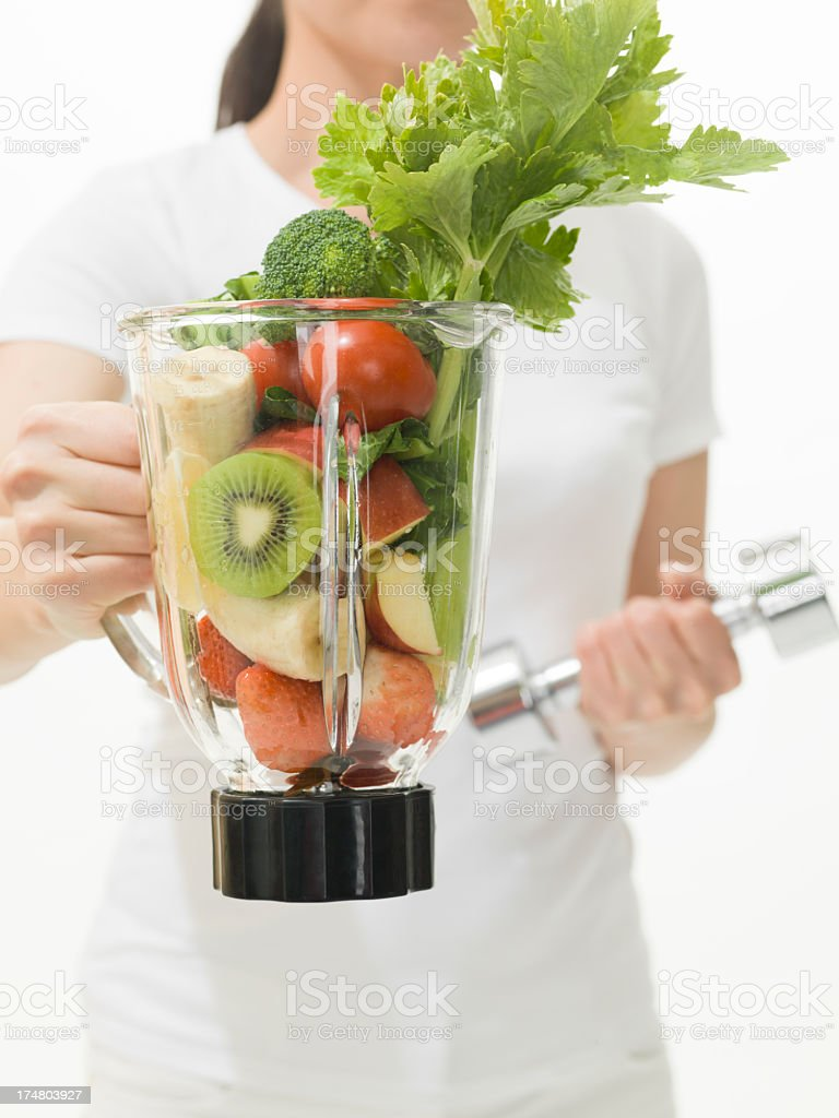 Woman holding Dumbbell and Vegetable juicer royalty-free stock photo