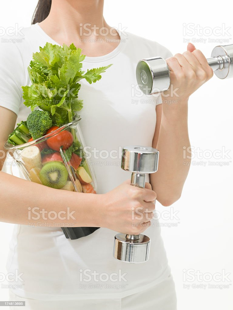 Woman holding Dumbbells and Vegetable juicer stock photo