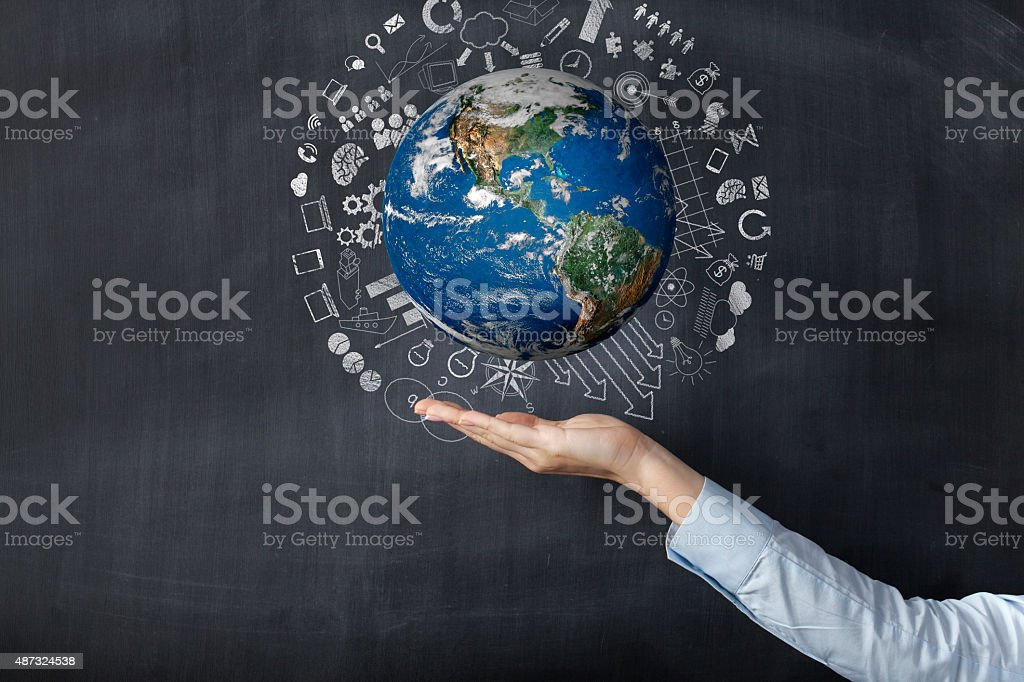 Woman holding earth front of blackboard stock photo