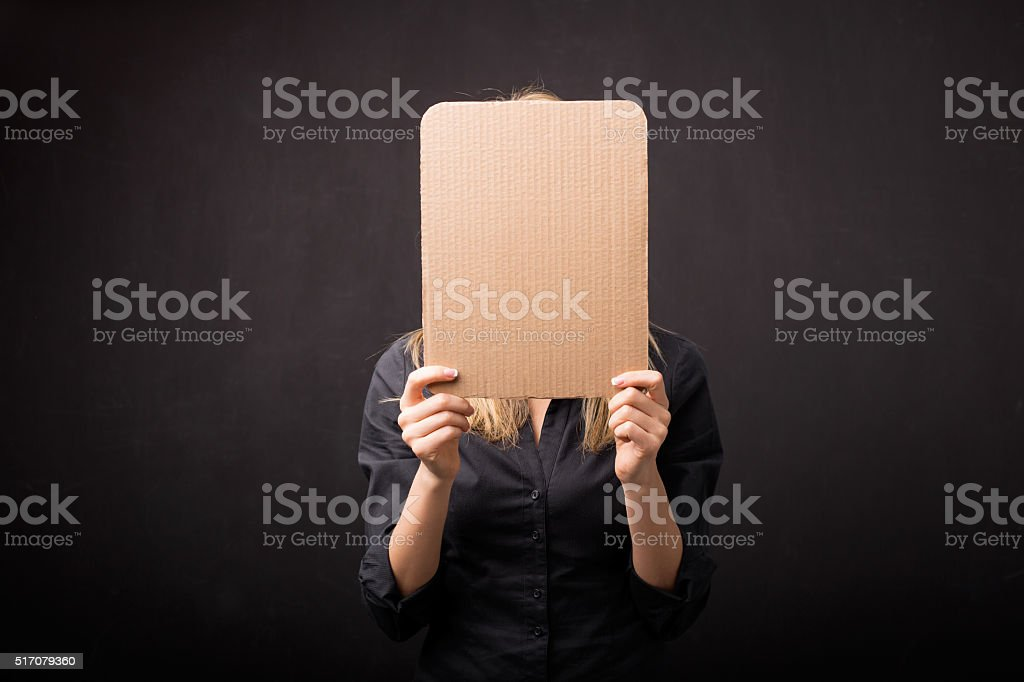 Woman holding empty cardboard in front of her face stock photo