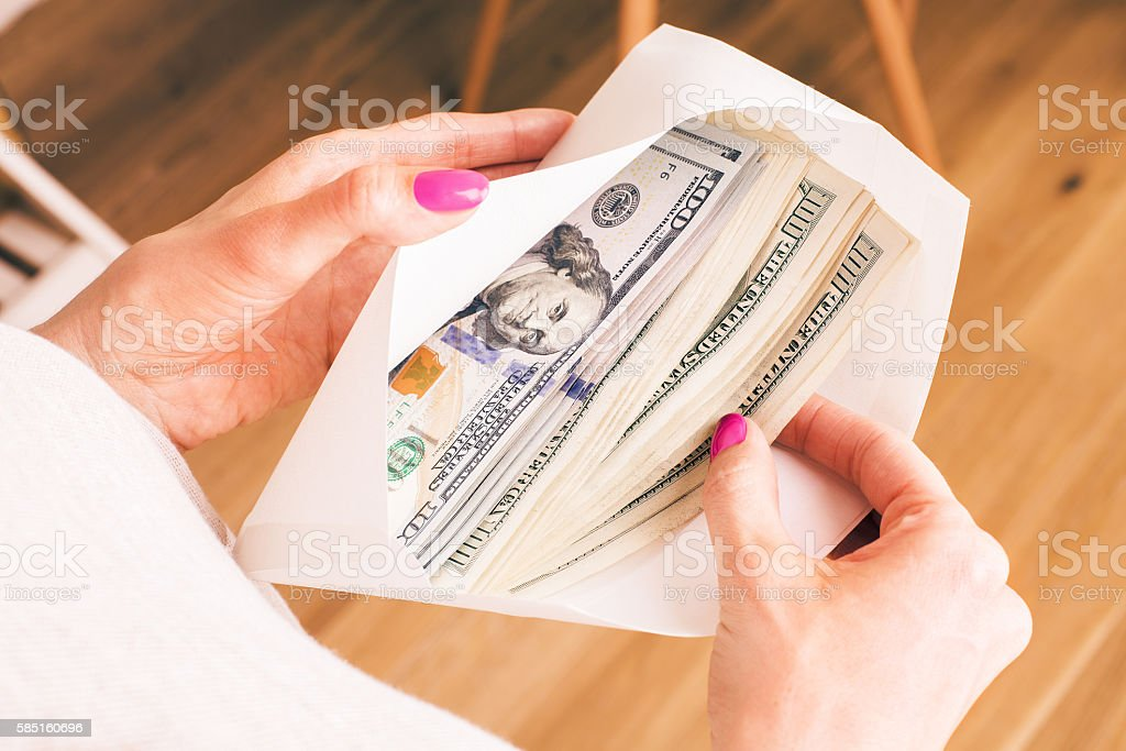 Woman holding envelope with cash stock photo