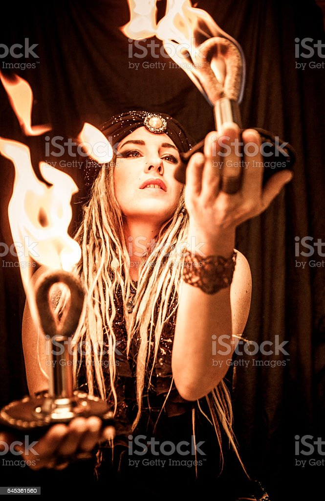 Woman Holding Fire Palm Torches stock photo