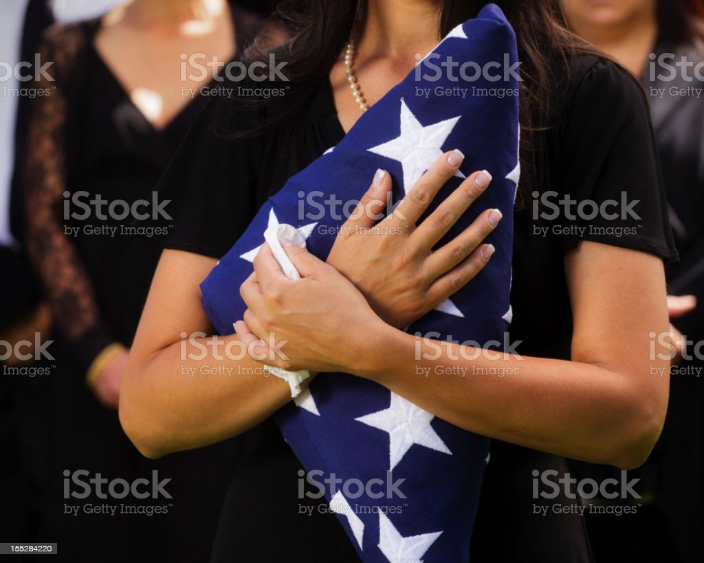 Woman Holding Flag at a Funeral stock photo