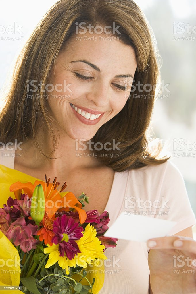 Woman holding flowers and reading note stock photo