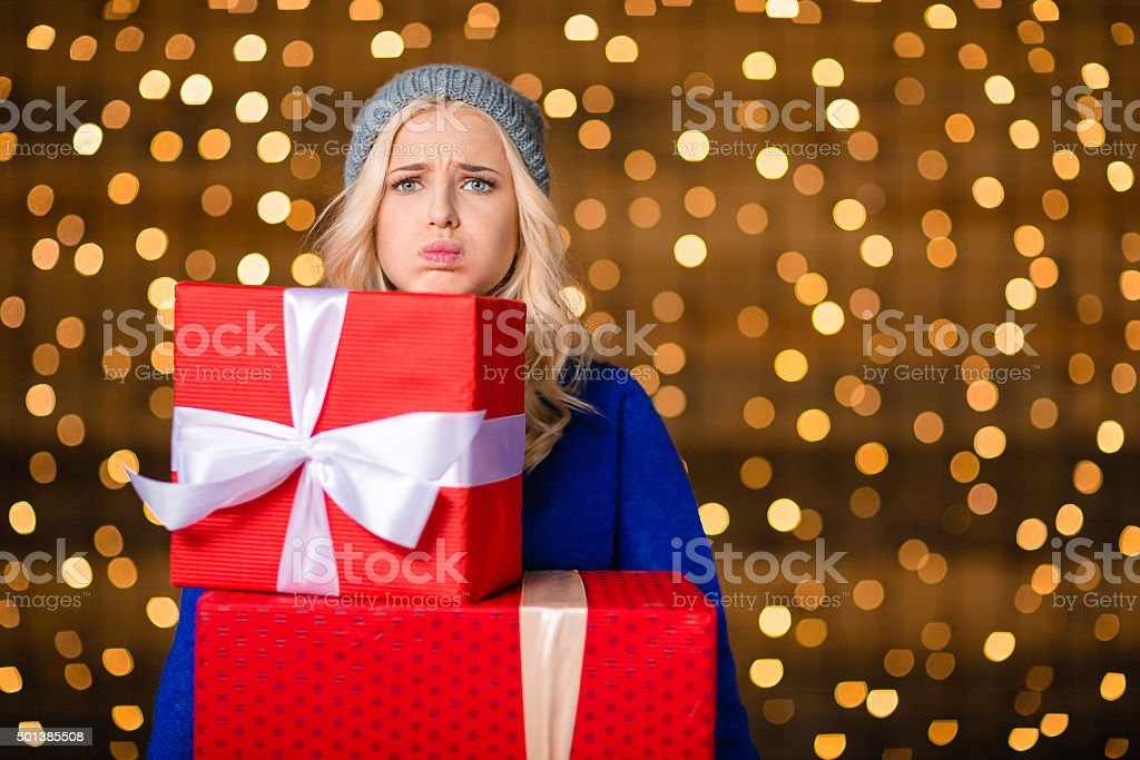 Woman holding gift boxes over holidays lights background stock photo
