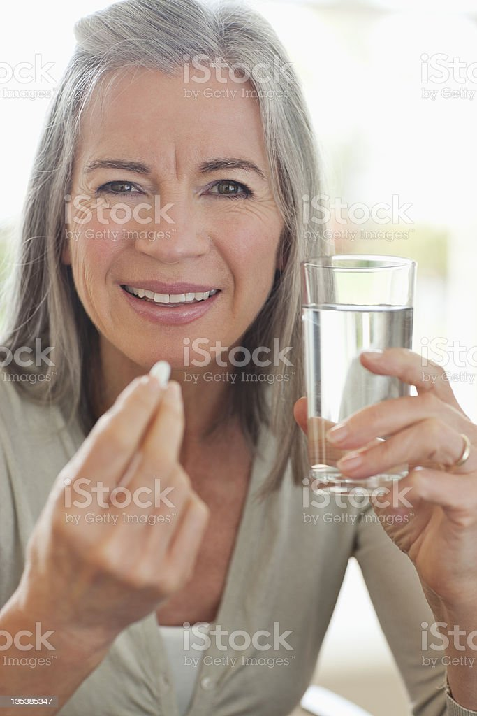 Woman holding glass of water and taking pill stock photo