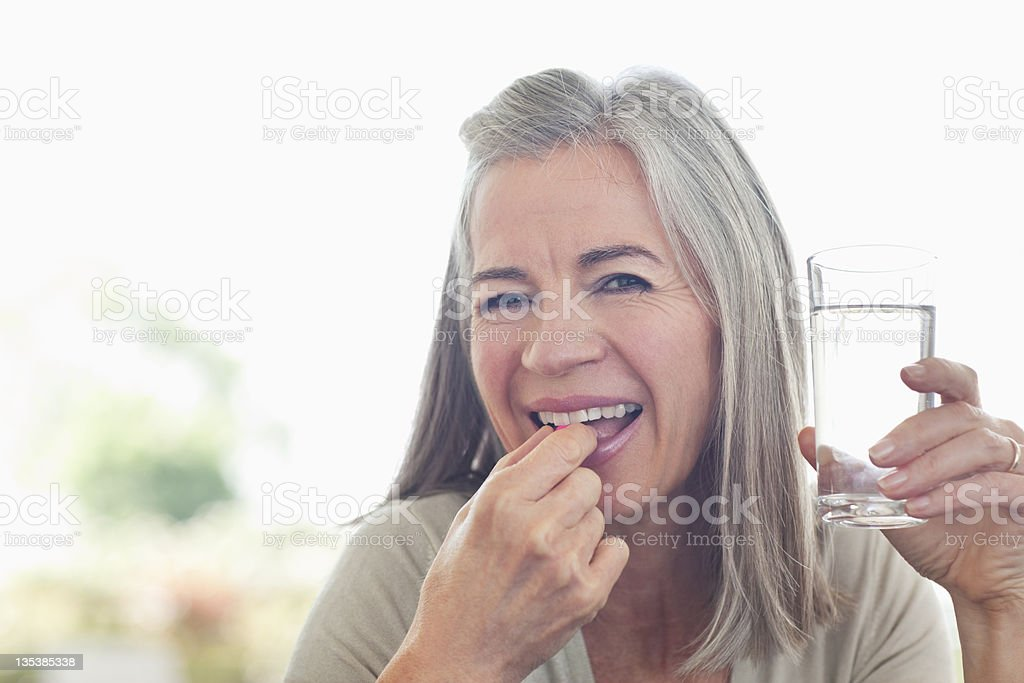 Woman holding glass of water taking pill stock photo