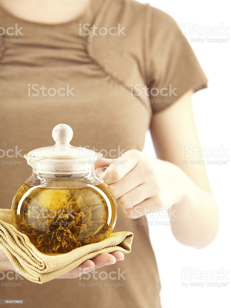 Woman holding glass teapot filled with herbal tea stock photo