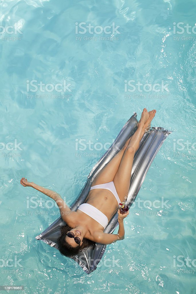 Woman holding glass while lying on raft stock photo