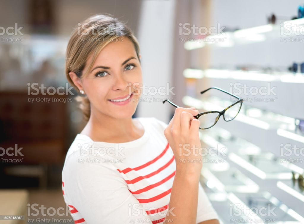 Woman holding glasses at the optician's shop stock photo