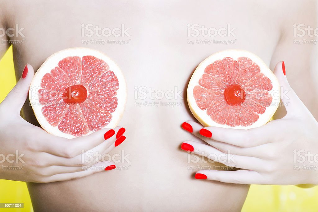 woman holding grapefruit in front of her breast stock photo