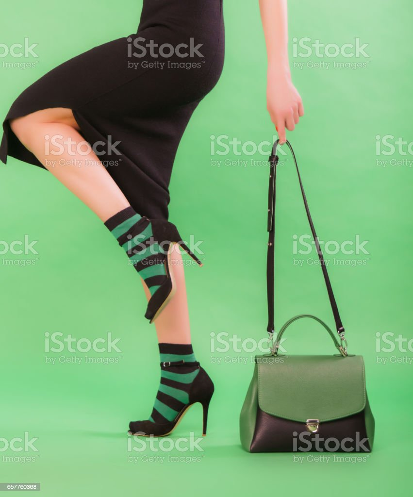 Woman holding green and black handbag stock photo