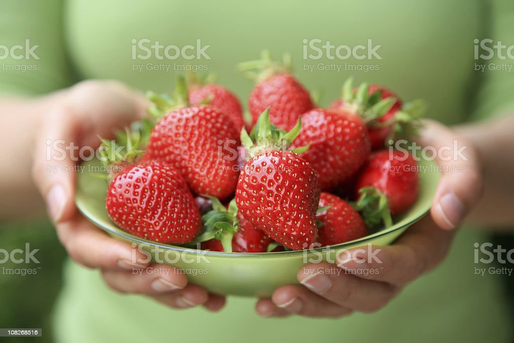 Woman Holding Green Glass Bowl of Strawberries royalty-free stock photo