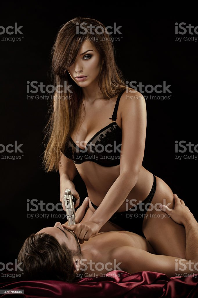 woman holding gun sitting on man in bed stock photo