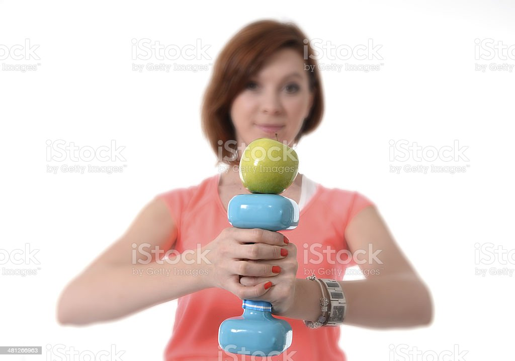 woman holding gym weight and apple in healthy nutrition concept royalty-free stock photo