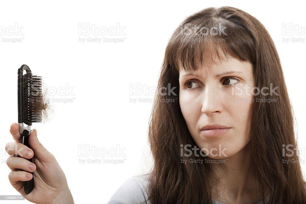 Woman holding hair brush full of hair stock photo