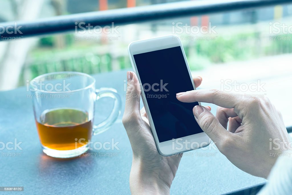 Woman Holding Hand Mobile Phone in a Coffee Shop stock photo
