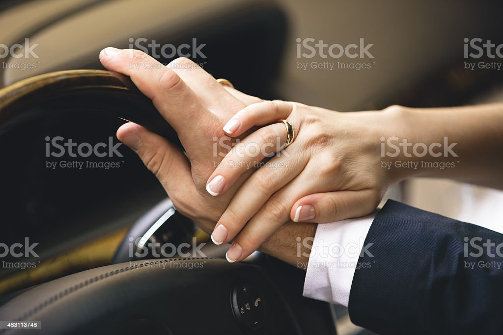 woman holding hand on men while he drives a car stock photo