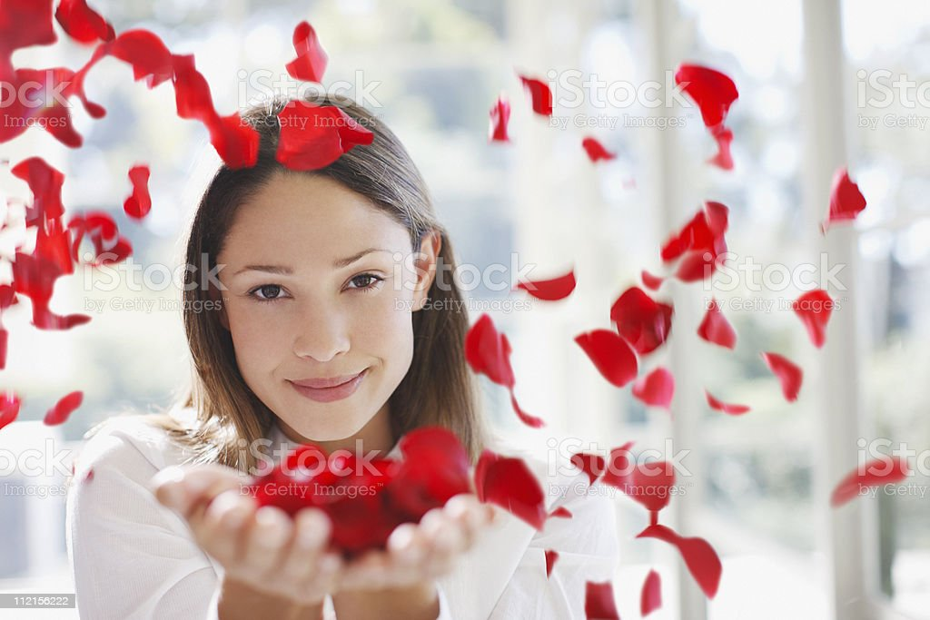 Woman holding handful of flower petals stock photo