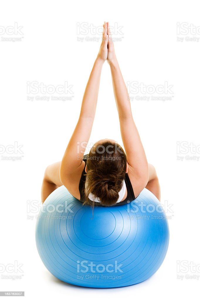 Woman holding hands together in the air on a yoga ball royalty-free stock photo