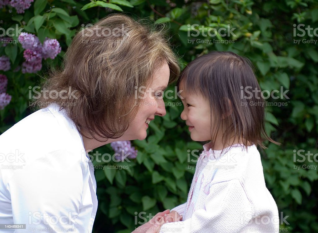 Woman holding hands with a young girl and smiling to her stock photo
