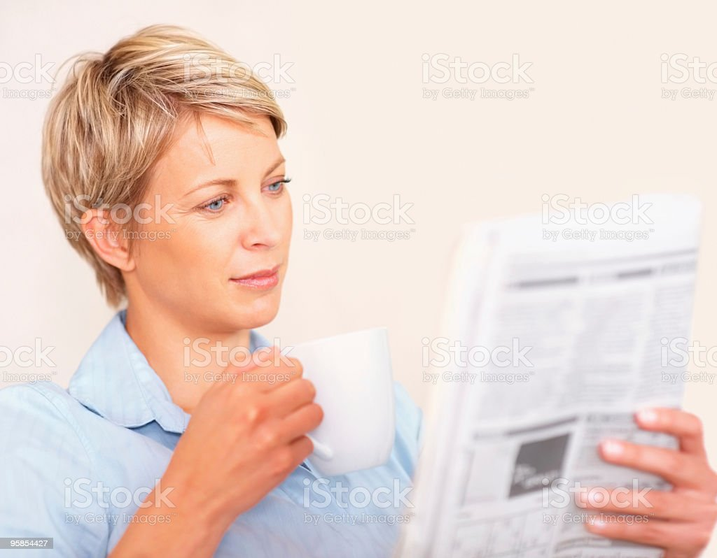 Woman holding having a cup of coffee and reading newspaper royalty-free stock photo