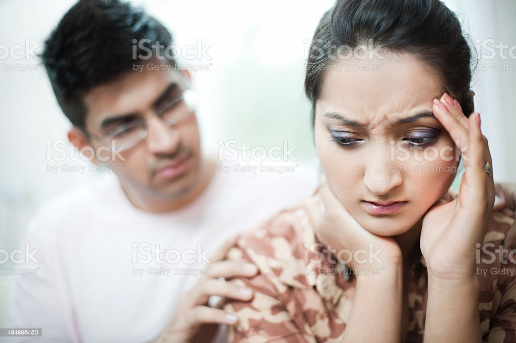 Woman holding head with depression and headache, man consoling. stock photo