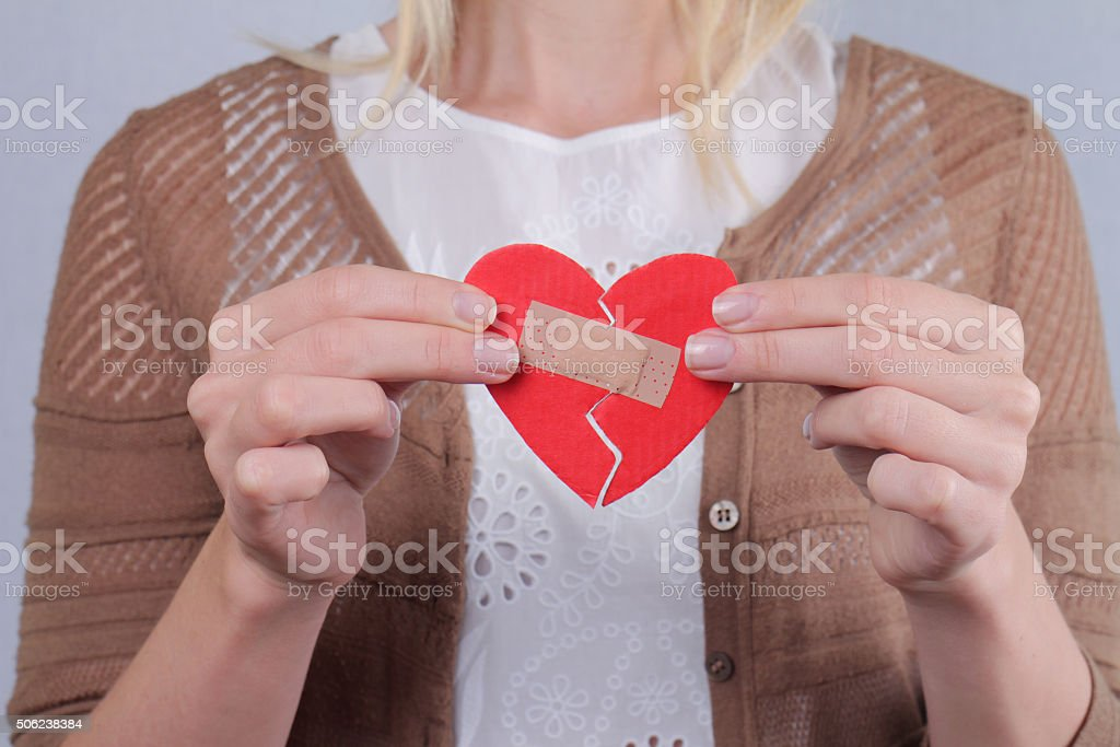 Woman holding  heart fixed by plaster . Feelings and emotions. stock photo